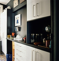 The small, modern kitchen has white built-in units set against blue walls