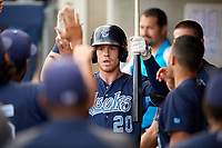 Corpus Christi Hooks designated hitter Drew Ferguson (20) is congratulated by his teammates in the dugout after hitting a home run in the top of the first inning during a game against the Tulsa Drillers on June 3, 2017 at ONEOK Field in Tulsa, Oklahoma.  Corpus Christi defeated Tulsa 5-3.  (Mike Janes/Four Seam Images)