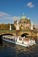 Berlin, Germany.  Berliner Dom seen across the Schlossbruecke, designed by K. F. Schinkel in 1821 with statues of gods and warriors.  Tourist sightseeing boat on the Spreekanal.