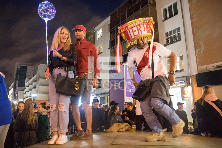 YEKATERINBURG, RUSSIA - June 21, 2018: A Peru dances on ul Malysheva road while Russians look on after his team lost against France during a 2018 FIFA World Cup group stage at Yekaterinburg Arena Stadium.