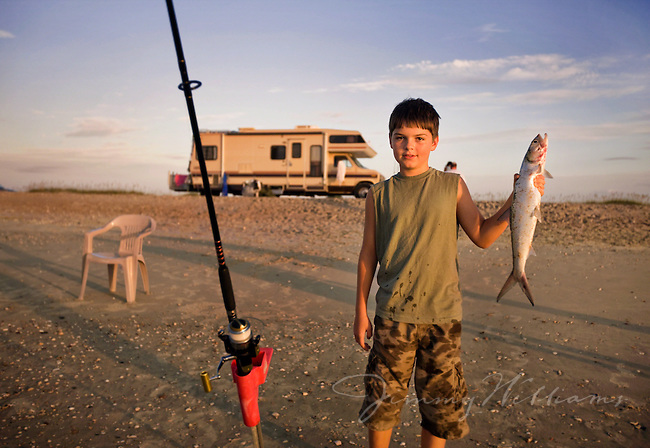 A boy proudly shows off a fish he caught while staying with family on the coast of North Carolina