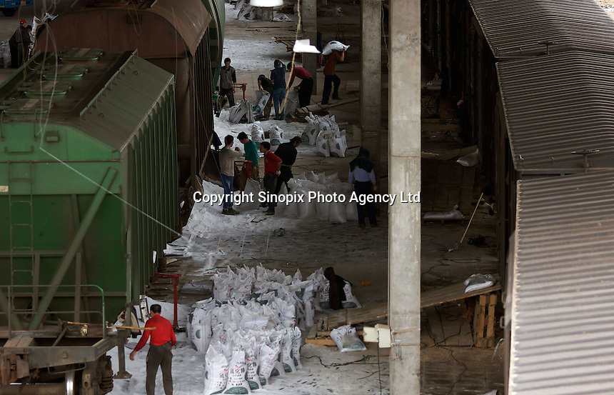 Workers collect fertilizer powder that the package has been broken, in the Manzhouli railway station, Inner Mongolia, China..29 May 2008