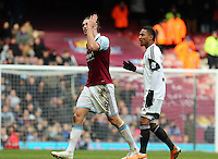 Pictured: Andy Carroll of West Ham (L) is protesting having been shown a red card by match referee Howard Webb for his header challenge against Chico Flores of Swansea. 01 February 2014<br />