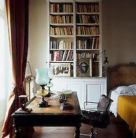 A traditional bedroom with an antique bed. A desk and chair arrangement in front of a window provides a study area within the room. A collection of books are displayed on shelves above a cupboard. Two Victorian oil lamps stand on the desk.