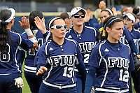 11 February 2012:  FIU's team (pictured, Alex Casals (13), Erika Arcuri (12)) high-five as part of a pre-game ritual.  The University of Louisville Cardinals defeated the FIU Golden Panthers, 4-2, as part of the COMBAT Classic at the FIU Softball Complex in Miami, Florida.