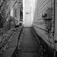 White modern doorway down leaf covered stone walkway<br />