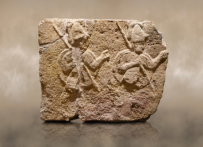 Photo of Hittite relief sculpted orthostat stone panel of Long Wall Limestone, Karkamıs, (Kargamıs), Carchemish (Karkemish), 900-700 B.C. . Anatolian Civilisations Museum, Ankara, Turkey. Two helmeted soldiers in short skirt carry shield on their backs and spear in their hands.<br /> <br /> On a brown art background.