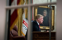 President Donald Trump is seen through the window of the Oval Office as he delivers a primetime address on the government shutdown and his funding request for over $5 billion for a southern border wall, at the White House in Washington, D.C. CAP/MPI/RS<br /> &copy;RS/MPI/Capital Pictures