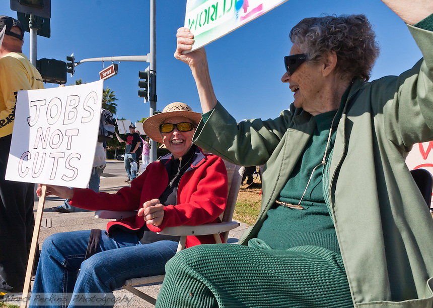 Cov (left) and Virginia (right) sit in lawn chairs while holding signs at the Occupy Orange County, Irvine camp on November 5.