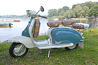 A restored white and blue vintage Lambretta scooter (model 'Li' series 2, 150 cc, circa 1961) parked on the grass of a lake's shore with boats in the background.