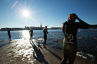 25 AUG 2013 - STOCKHOLM, SWE - Competitors prepare to enter the water for their wave start of the Stockholm Triathlon in Stockholm, Sweden (PHOTO COPYRIGHT © 2013 NIGEL FARROW, ALL RIGHTS RESERVED)