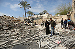 Palestinians inspect a security Hamas site that was damaged in an Israeli airstrike in Gaza city, on March 26, 2019. Israeli forces carried out strikes across the Gaza Strip, after an earlier rocket attack that destroyed a family home and wounded seven people in a neighbourhood north of Tel Aviv. The army also said it was reinforcing troops along the Gaza border and calling up reserves. Photo by Ashraf Amra