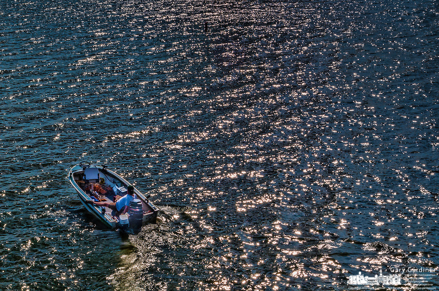 A fisherman navigates his small craft toward the shoreline in the late afternoon sun on Hoover Reservoir in Columbus, Ohio.