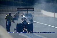Nov. 11, 2012; Pomona, CA, USA: NHRA safety safari crew tends to a top fuel dragster on the track with oil behind the dragster during the Auto Club Finals at at Auto Club Raceway at Pomona. Mandatory Credit: Mark J. Rebilas-