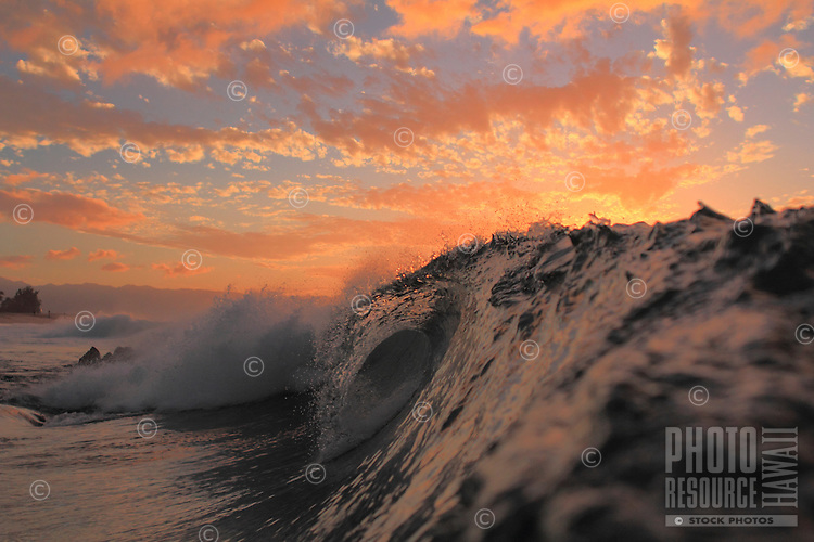 Watercolor sky behind a breaking wave at Rockpiles on the North Shore of O'ahu.