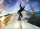 USA, California, San Francisco, Fort Point, surfer on a wave at Fort Ponit Surf Break in front of the Golden Gate Bridge, Sunset