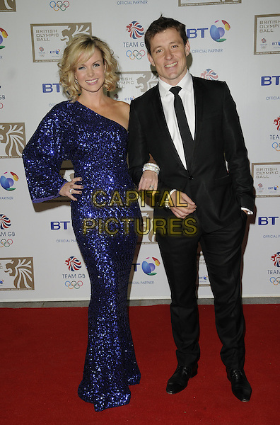 AMANDA HOLDEN & BEN SHEPHARD.At the British Olympic Ball, Grosvenor House hotel, Park Lane, London, England, 24th September 2010..full length black suit tie white shirt arm in arm one sleeve shoulder blue dress long maxi sequined sequin hand on hip.CAP/CAN.©Can Nguyen/Capital Pictures.