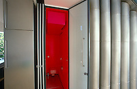 In a London house designed by Richard Rogers stainless steel has been used for an industrial aesthetic with softer areas of bright colour such as a loo painted bright pillar box red