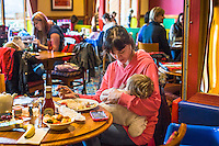 A mother eats her dinner while breastfeeding her child in the family restaurant and play area of a pub.
