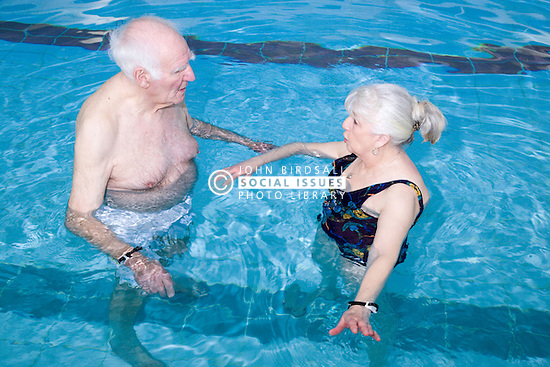 Two older people having a chat whilst at the swimming pool at their local leisure centre,
