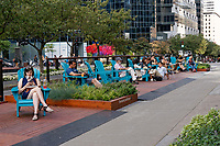 People sitting outdoors on McGill College Avenue, part of the promenade fleuve-montagne pedestrian walkway, Montreal, Quebec, Canada