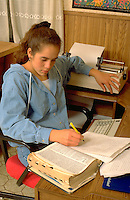 Tongan American age 16 writing paper on computer in her home.  St Paul Minnesota USA