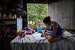 Geovana Batista de Sousa, 11, studies in her family's home in the middle of the Amazon River near Santarem, Brazil. Her family is one of the last holdouts in an area where land is being bought up to build a large port facility.