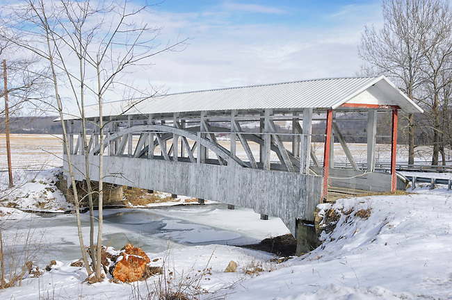Covered bridge in white winter snow, weathered and worn under sunny cold skies.