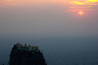 The Mount Popa Temple in Myanmar, a complex of monasteries, stupas and shrines on top of an impressive rocky volcanic plug reached by 770 steps, presents a romantic picture in a partly cloudy sunset.