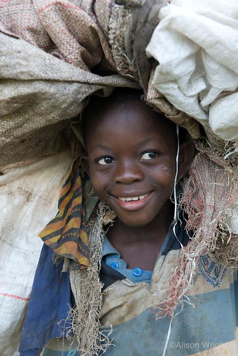 Boy carrying garbage. Waterloo, Sierra Leone, Africa