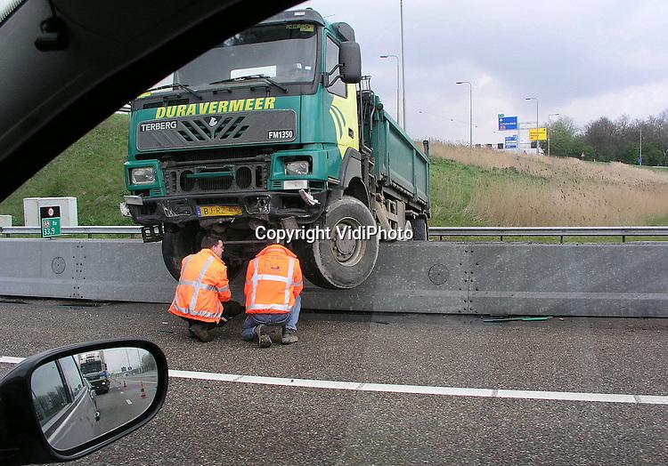 Foto: VidiPhoto..BADHOEVEDORP - Een met zand geladen kiepwagen van bouwonderneming Dura Vermeer is woensdagmiddag op het knooppunt Badhoevedorp bovenop de vangrail beland. De chauffeur verloor bovenaan de lus van het knooppunt de macht over het stuur, terwijl hij (handsfree) aan het bellen was. De vrachtwagenchauffeur kwam met de schrik vrij. Bij het ongeval is 200 liter diesel weggestroomd, waardoor het zoab-wegdek spiegelglad is geworden. De rijstrook is zes uur lang afgesloten geweest voor alle verkeer.