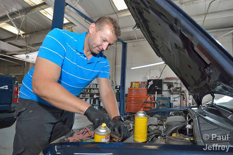 Vadim Yavny, a resettled refugee from Ukraine, works in an automotive repair shop in Harrisonburg, Virginia, on July 18, 2017. He was resettled in the community in the 1990s by Church World Service. <br /> <br /> Photo by Paul Jeffrey for Church World Service.