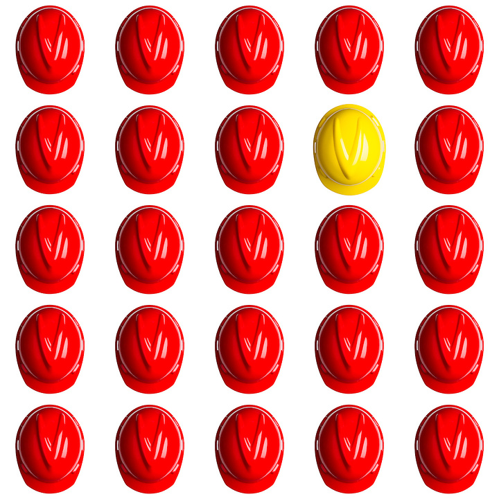 yellow helmet surrounded by various red hardhats symbolizing the spain