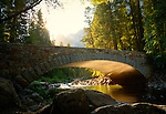 California, Yosemite National Park. Morning sun rises over the Seirra Nevada Mountains and reflects off the water of the Merced River illuminating the underside of an arched bridge.