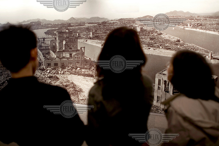 Visitors examine a photograph that shows the city of Hiroshima in the aftermath of the 6 August 1945 atomic bomb detonation. The Hiroshima Peace Memorial (Genbaku Dome) is clearly visible an was the only building left standing at the hypocentre of the bomb blast following the detonation of the 'Little Boy' atomic bomb, dropped on 6 August 1945. /Felix Features