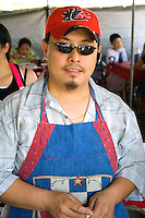 Hmong cook in outdoor restaurant wearing colorful apron and cap. Hmong Sports Festival McMurray Field St Paul Minnesota USA