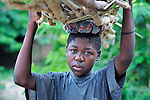 """A woman carries a load of firewood on her head in Chidyamanga, a village in southern Malawi that has been hard hit by drought in recent years, leading to chronic food insecurity, especially during the """"hunger season,"""" when farmers are waiting for the harvest."""