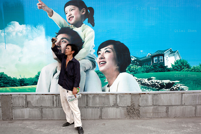 A man uses his cellphone to take a picture while standing in front of a poster depicting a happy one-child family in Shanghai, China on 27 July 2009.  As China's largest city age rapidly, city family planning officials have begun to actively encourage young couples who are themselves both only child to have two kids. First implemented in 1979, the one-child policy has lessened an estimated 400 million fewer births in China.