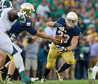 Quarterback Tommy Rees (11) hands off to running back Cam McDaniel (33) as the Irish kill the clock.