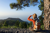 Spain, Canary Islands, La Palma, view at vulcano San Antonio near village Los Canarios Fuencaliente, woman with backpack hiking, taking a break