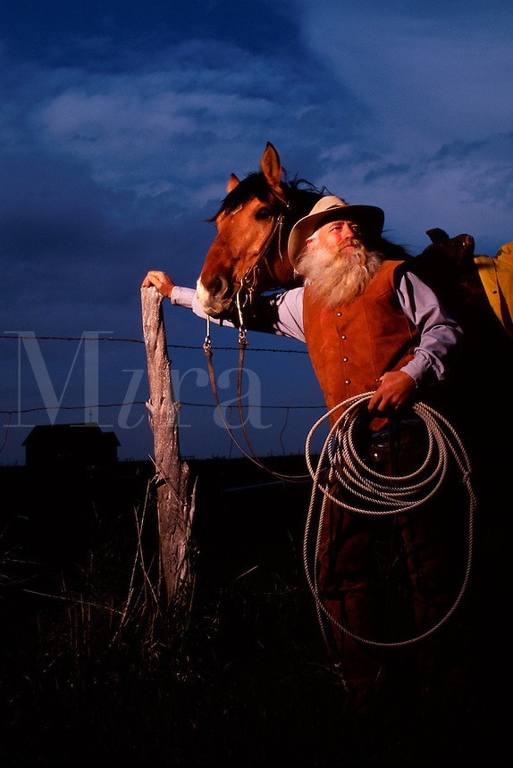 A cowboy rancher and his horse as he leans against a fence and holds his roping lariat. South Dakota.