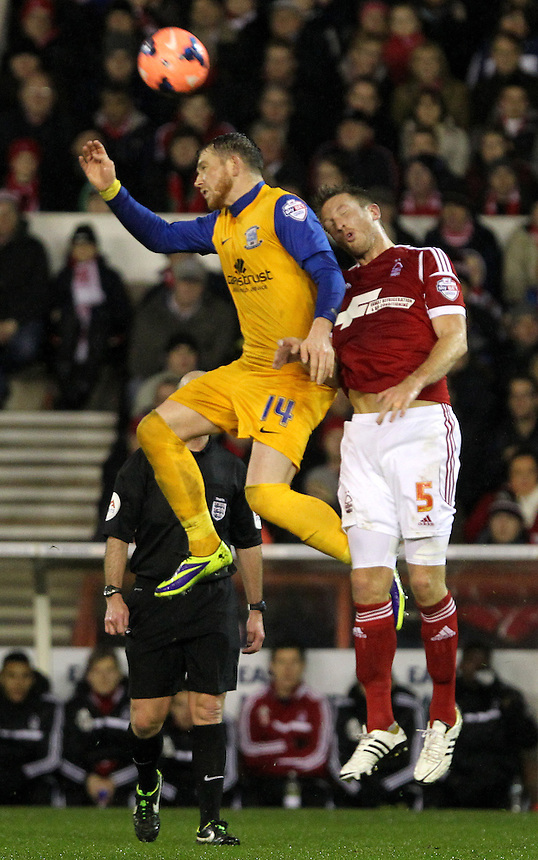 Preston North End's Joe Garner jumps with Nottingham Forest's Danny Collins<br />