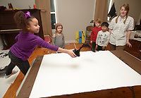 NWA Democrat-Gazette/ANDY SHUPE<br /> Layla Sisemore, 8, (left) slings paint onto a canvas Wednesday, Jan. 3, 2018, as instructor Heather Younger Morton (right) watches during BLACKOUT, a youth art camp at Artist's Laboratory Theatre in Fayetteville. The eight-day pay-what-you-can camp is exploring the affect of light and dark through art, performance and science experiments and runs through Friday.