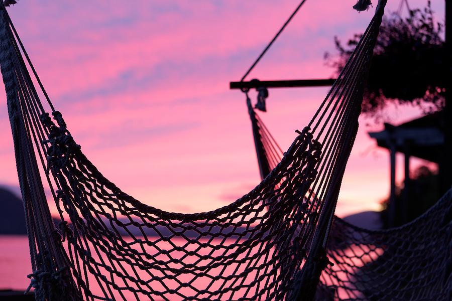 Fishnet hammocks silhouetted against pink sunset, Sitka, Alaska, USA