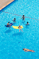 Spain. Ibiza in the Balearic islands. Ibiza. Tourists (men and women) swimm, take a rest on inflatable mattress, talk and sunbathe in a swimming pool in Ibiza City. Mediterranean sea. © 1999 Didier Ruef
