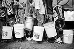 People wait in line to fill buckets with clean water from a truck in a camp for those displaced by the recent earthquake in Petionville, outside Port-au-Prince, Haiti.