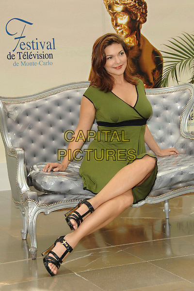 "LAURA HARRING.Photocall promoting the television series ""The Shield"" during the fourth day of the 2008 Monte Carlo Television Festival held at Grimaldi Forum, Monaco, Principality of Monaco,.June 11th, 2008..full length green dress black strappy shoes sandals sitting.CAP/TTL .©TTL/Capital Pictures"