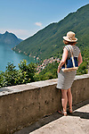 A woman wearing a straw hat admires the view of Lake Lugano from the Italian town of Castello, a town built on the ruins of a castle on the hills above Lake Lugano