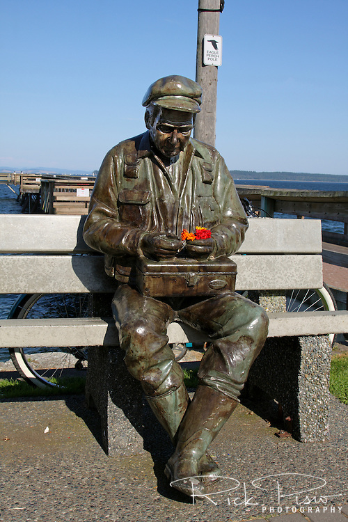 A statue of a fisherman sitting on a bench while holding a small bouquet of flowers in Sydney, British Columbia.
