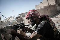 A rebel fighter belonging to the Kateba Omar Ben Abdul Aziz fires his kalashnikov to the enemy's position at the Aamria battlefield embedded inside a civilian neighborhood at the southwest of Aleppo City.